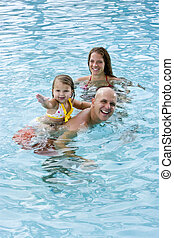 Family with young child playing in swimming pool - Family...