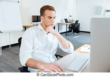 Thoughtful young businessman using computer at work -...