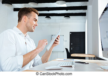 Happy young businessman using tablet in office