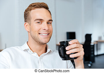 Happy handsome young businessman drinking coffee in office -...