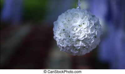 ball of white flowers hanging on a ribbon