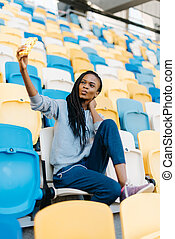 Beautiful sports african american woman with puckering lips making selfie photo on smartphone at stadium, plastic seats as background