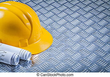 Rolled blueprints hard hat on fluted metal background copy space