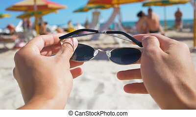 man putting on sunglasses on the beach first-person view
