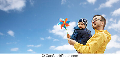 happy father and son with pinwheel toy outdoors - family,...