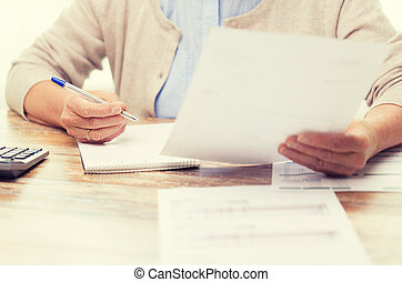 senior woman with papers and calculator at home - business,...