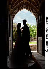 Wedding couple in church entrance - Young wedding couple...