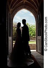 Wedding couple in church entrance - Young wedding couple...