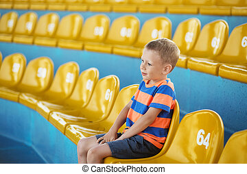 Child take own seat in the stadium or dolphinarium and...