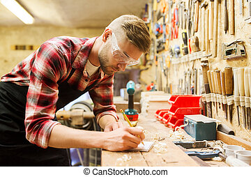 carpenter writing to notebook at workshop - profession,...