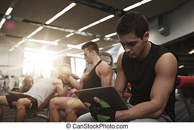 group of men with tablet pc and dumbbells in gym - sport,...