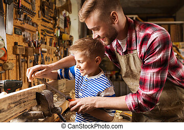father and son with rasp working at workshop - family,...