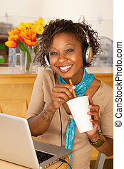 Young Woman Drinking Beverage and Using Laptop - A young...