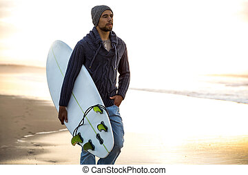 Surfing is a way of life - A surfer with his surfboard...