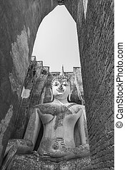 Black and white view of Old sitting buddha statue through...