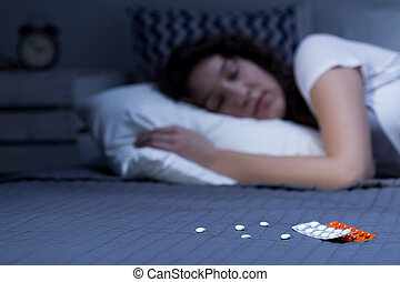 Sleeping pills on bed and sleeping woman in the background