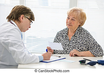 Doctor and patient - Doctor prescribes medication to the...