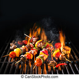Meat kebabs with vegetables on flaming grill - Barbecue...