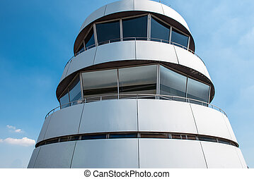 Tower of airport with large windows against blue sky