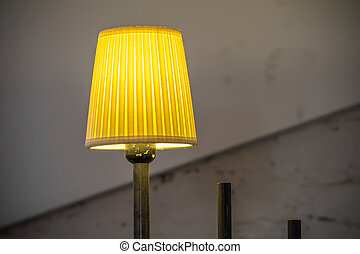 Closeup with lighted yellow lamp. Yellow vertical lighted lamp with old walls behind.