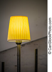 Closeup with lighted yellow lamp. Vertical view with yellow lighted lamp and old walls behind.