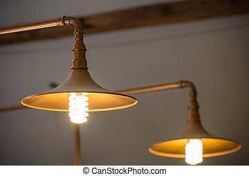 Closeup with two metallic lamps. Two golden metallic lighted lamp hanging on pipes.