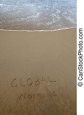 Global warming written in the sand at beach with rising wave