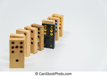 Wooden dominoes with black plastic domino on white...