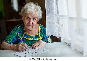 Retired woman fills out utility bills sitting at home behind...