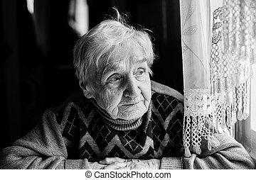 Elderly woman portrait looking out the window....