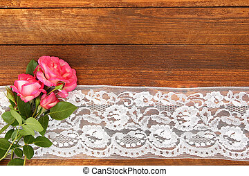 flowers roses on a wooden background with lace - beautiful...