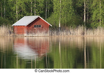 Boathouse at a Swedish lake with reflections