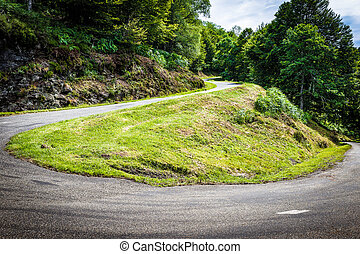 Winding road with sharp bend going up the mountain in the...