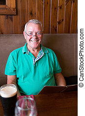 Smiling senior man holding a restaurant menu and having a...