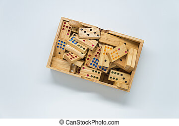 Wooden dominos in wooden box on white background with...