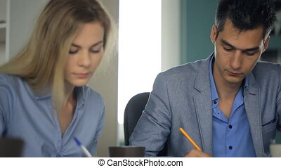 Two business persons are busy with paperwork in office.
