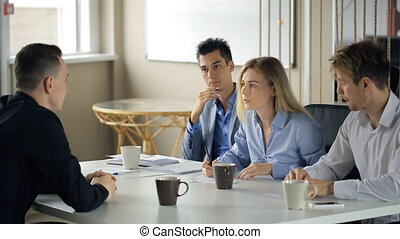 Office workers meet during coffee break to discuss working...