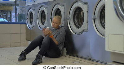 Woman using smart phone in the laundry - Young woman passing...