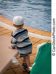Little boy standing next to the swimming pool on a chilly...