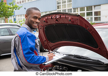 Mechanic With Clipboard In Front Of A Car