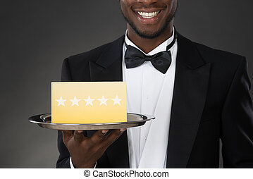 Waiter Holding Plate With Star Rating - Portrait Of African...