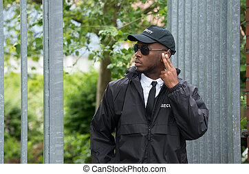Security Guard Listening To Earpiece - Young African Male...
