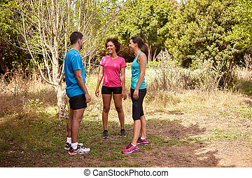 Three joggers talking on a break - Three young joggers...