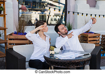 Happy business couple taking selfie at outdoor restaurant.