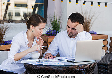 Young Business people tired working In Front Of Computer At Desk to cofee cafe