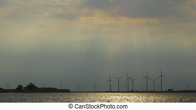Windmills on the river bank at sunset - Working wind...
