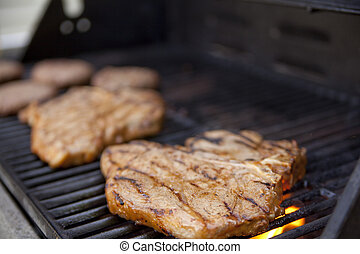 Grilling meat - Steaks and burgers on the grill. Shallow...