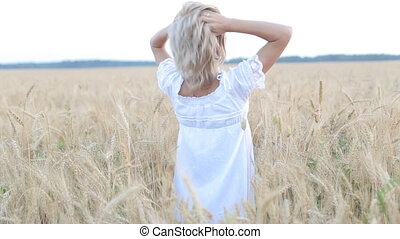 Beautiful young woman standing in a field of lifting her arms up