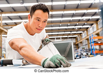 Asian worker in production plant on the factory floor -...