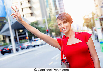 Businesswoman trying to catch a taxi in business city...